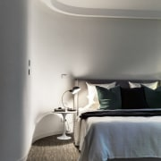 Curved walls lead the eye to the bed architecture, bed frame, bedroom, ceiling, daylighting, floor, flooring, furniture, home, house, interior design, lighting, room, wall, window, wood, gray