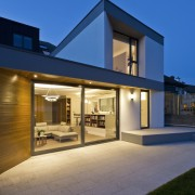 Large sliding glass doors welcome you into the architecture, building, elevation, estate, facade, home, house, property, real estate, residential area, siding, sky, window, blue