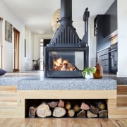 This clever fireplace features a small wood nook fireplace, hearth, home, home appliance, interior design, living room, wood burning stove, gray