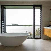This freestanding bathtub looks out over the bay architecture, bathroom, bathtub, floor, interior design, plumbing fixture, room, window, gray, white