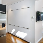 Storage is hidden away, flush with the wall cabinetry, door, floor, home appliance, interior design, kitchen, real estate, gray