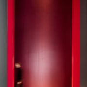 This massive doorway is certainly imposing - This door, floor, interior design, light, lighting, red, wall, red