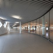 This hallway runs between the exterior wall and airport terminal, architecture, ceiling, daylighting, floor, leisure centre, lobby, metropolitan area, structure, gray