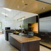Wood runs above the kitchen, breaking up the architecture, cabinetry, ceiling, countertop, floor, hardwood, interior design, kitchen, wood flooring, gray