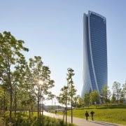 The new tower rises up above Milan - architecture, building, condominium, corporate headquarters, daytime, metropolitan area, sky, skyscraper, tower, tower block, tree, teal