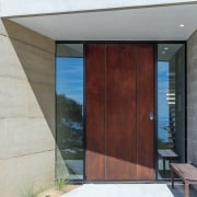 A weathering steel door is fit for a architecture, door, facade, house, real estate, window, gray