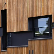 The structure around the windows helps with privacy architecture, facade, home, house, siding, wall, window, wood, brown, orange, black