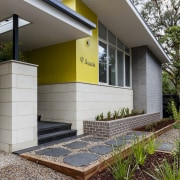 The yellow touches give the home a contemporary architecture, backyard, cottage, facade, home, house, property, real estate, residential area, siding, yard, gray, white