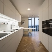 A herringbone wood floor perfectly complements the white apartment, architecture, cabinetry, countertop, cuisine classique, daylighting, floor, interior design, kitchen, property, real estate, room, gray