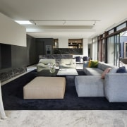 This expansive living room opens out to an floor, flooring, interior design, living room, property, real estate, gray
