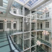 A large atrium features opaque glass floors - apartment, building, condominium, daylighting, glass, property, real estate, window, gray