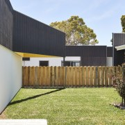 There's ample yard space in between the different architecture, backyard, courtyard, facade, fence, home, home fencing, house, outdoor structure, property, real estate, residential area, siding, yard