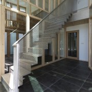A metal staircase leads you up to the architecture, baluster, daylighting, floor, flooring, glass, handrail, interior design, lobby, stairs, structure, tile, gray, black
