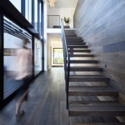 This wood staircase floats up to the second apartment, architecture, daylighting, floor, flooring, hardwood, home, house, interior design, loft, real estate, stairs, wood, wood flooring, black, gray