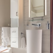Part of a beachside home bathroom renovation, this bathroom, bathroom accessory, bathroom cabinet, bathroom sink, ceramic, floor, plumbing fixture, room, sink, tap, toilet seat, gray