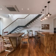 This kitchen features a waterfall island that appears ceiling, dining room, floor, flooring, hardwood, interior design, real estate, wood, wood flooring, gray, brown