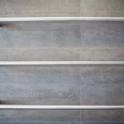 Heated towel rails provide an industrial touch in wood, gray