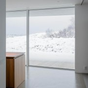 The home seems to hold the winter snow architecture, glass, home, house, interior design, window, white, gray