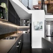 A bookshelf and sitting area sits above the architecture, countertop, daylighting, house, interior design, kitchen, loft, black, white