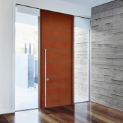 A weathering steel door contrasts with the concrete door, floor, interior design, wood, wood stain, gray, white