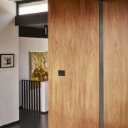 Wood walls provide a contrast with the white cabinetry, cupboard, door, floor, furniture, hardwood, interior design, sliding door, wall, wardrobe, wood, wood flooring, wood stain, orange