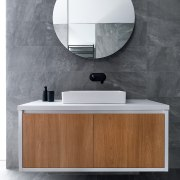 A cantilevered, clean-lined vanity cabinet and accompanying round architecture, bathroom, bathroom accessory, bathroom cabinet, ceramic, chest of drawers, floor, flooring, furniture, interior design, material property, mirror, room, sink, tap, tile, wall, wood, gray