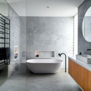 Natural-look materials, a freestanding tub, a cantilevered vanity architecture, bathroom, bathtub, bidet, building, ceramic, floor, flooring, house, interior design, material property, plumbing fixture, property, room, tap, tile, wall, gray