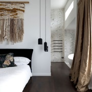 Rich timber floors run between bathroom and bedroom white, gray
