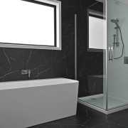 The spa-like guest bathroom includes honed Nero tiles