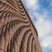 The curvature of the facade form represents the architecture, blue, building, cloud, daytime, design, facade, landmark, line, pattern, sky, symmetry, brown, gray