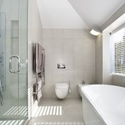 View of the ensuite bathroom which features an architecture, bathroom, daylighting, floor, interior design, product design, real estate, room, tap, tile, gray