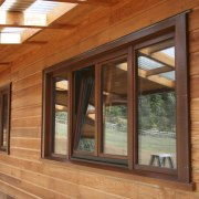 View of windows set into timber joinery by beam, door, facade, home, house, log cabin, lumber, real estate, siding, wall, window, wood, wood stain, brown, orange