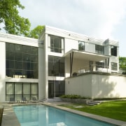 View of white home and pool. architecture, building, condominium, corporate headquarters, elevation, estate, facade, home, house, property, real estate, residential area, window, white, green
