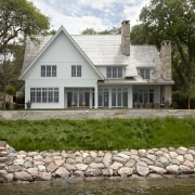 A prime lakefront setting and mature trees enhance cottage, estate, facade, farmhouse, home, house, property, real estate, tree, water, brown, white