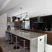 The clean-lined kitchen in this renovated home has architecture, ceiling, countertop, floor, house, interior design, kitchen, table, white, gray