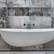 Supported by a ledge and pedestal, this tub bathtub, floor, plumbing fixture, tap, tile, gray