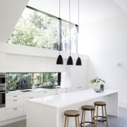 Architect Eva-Marie Prineas prioritised the owners' modest renovation architecture, countertop, daylighting, floor, furniture, home, house, interior design, kitchen, product design, table, white