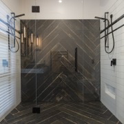 Contributing to this master suite's dramatic black and bathroom, floor, flooring, glass, interior design, plumbing fixture, room, shower, tile, wall, gray, black