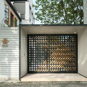 A black-and-bronze woven metal gate, inspired by a door, facade, gate, gray, white