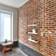 An original brick wall was exposed and sealed brick, brickwork, floor, flooring, interior design, real estate, wall, gray, brown