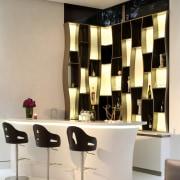 A backdrop comprised of internally lit alcoves sets furniture, interior design, light fixture, product design, table, orange