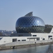 The glass and timber ovoid shape of the architecture, building, city, daytime, reflection, river, sky, water, teal, gray
