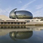Architect Shigeru Ban designed the dramatic music venue architecture, building, convention center, corporate headquarters, daytime, headquarters, reflection, river, sky, structure, water, water resources, teal