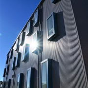 Te Ara o Mauao includes metal cladding and architecture, building, commercial building, corporate headquarters, daytime, facade, headquarters, home, house, residential area, sky, structure, window, black, blue