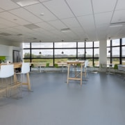 Armstrong Ultima ceiling tilesideally complement the Sistema building architecture, cafeteria, classroom, daylighting, institution, interior design, table, gray