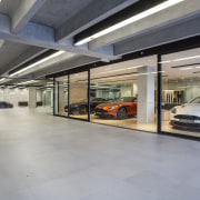 Large-format, matt concrete pavers provide a unifying refined automotive design, car, car dealership, executive car, garage, luxury vehicle, motor vehicle, parking, gray