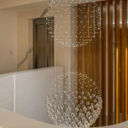 Delicate pendants decorate the top of the stairs architecture, ceiling, flooring, glass, handrail, interior design, lighting, property, brown