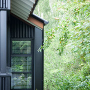 On this cedar- and metal-clad home, the black architecture, backyard, cottage, courtyard, door, facade, home, house, real estate, shed, siding, window, yard, green