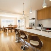 Featuring contemporary architectural lines, this home was built apartment, countertop, floor, flooring, hardwood, interior design, kitchen, property, real estate, room, wood flooring, white, brown