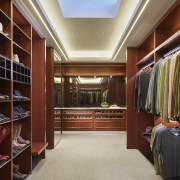With no windows, this large closet is the bookcase, cabinetry, ceiling, closet, flooring, furniture, interior design, lobby, room, wardrobe, red, gray